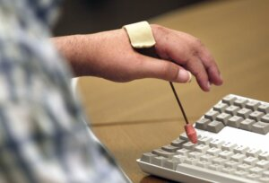 A hand outfitted with a simple assistive device for pressing keys on a computer keyboard.