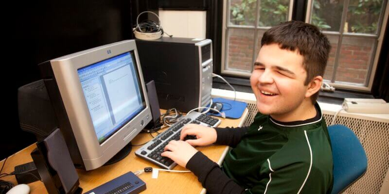 Blind young man uses a special keyboard while operating a computer